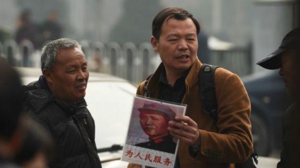 """Một người dân Trung Quốc cầm trong tay một bức hình của cố Chủ tịch Trung Quốc Mao Trạch Đông với dòng chữ đề """"Phụng sự nhân dân"""" bên ngoài một Văn phòng tiếp người dân khiếu nại."""